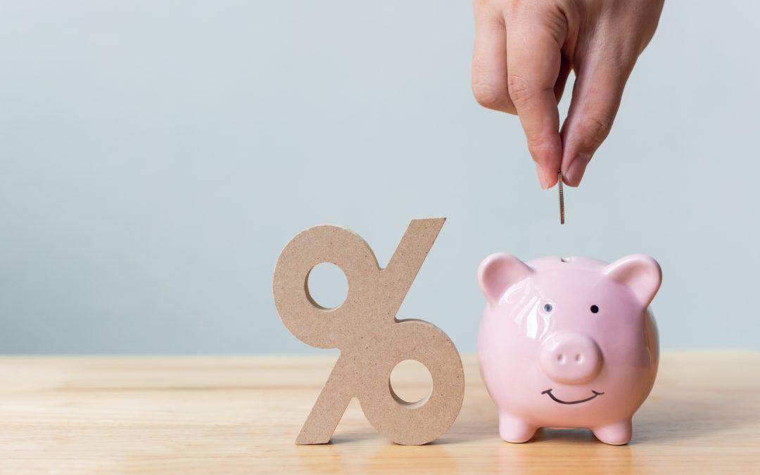 Hand putting money coin in piggy bank